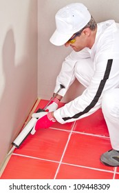 worker in white clouts lays silicone sealant corner wall floor