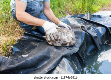 Worker in white gloves put a black vinyl sheet cover hole on the ground to be used as a pond for fish