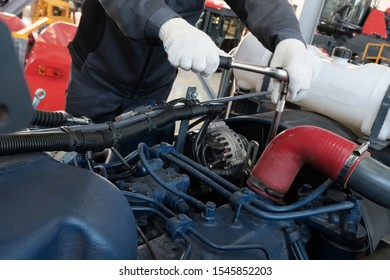 A worker in white gloves tightens a bolt or nut with a socket wrench. Plant for the production of machinery or car service. Repair of engines of tractors and cars. Industrial zone.