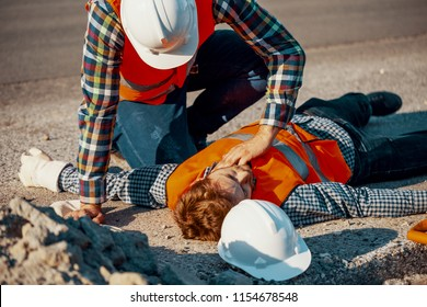 Worker in white helmet checking life functions of an injured man during roadworks