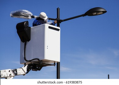A worker in a white helmet is installing a new street lamp