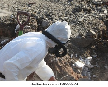 Worker with white protective suit, gloves and mask removes removal white asbestos on construction site. Demolition building, caution hazard. Action picture, part of a serie.