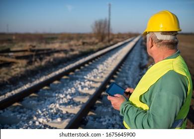 Arbeiter, der fotografiert alte Schiene. Ingenieur für Eisenbahnbauarbeiten