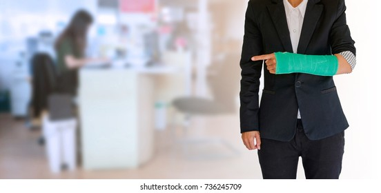 worker woman accident on arm with green arm cast on blurred business office working space background
