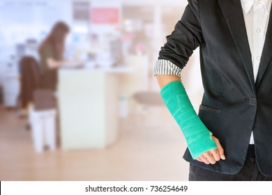 worker woman accident on arm with green arm cast on blurred business office working space background.