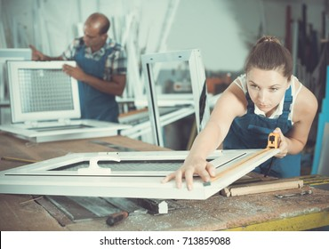 Worker woman is checking dimensions of finished plastic window using measuring tape at factory.