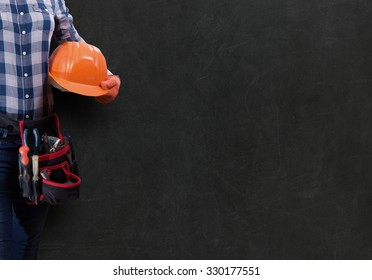 Worker woman with toolbelt and helmet against dark background
