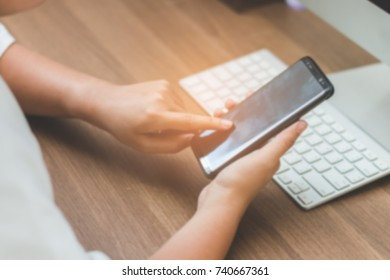The worker woman touching screen on smart phone blurred image