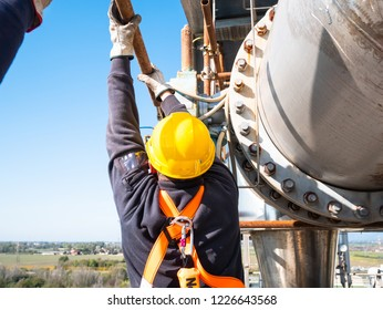 worker at work at height with personal protective equipment during maintenance operations of an industrial plant of a remotely controlled electric valve next to a flange with many bolts, in the backgr