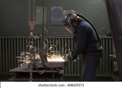 worker working with a angle grinder inside a factory