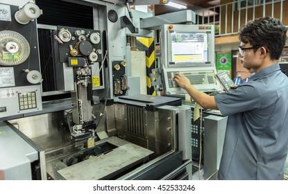 Worker working with cnc machine at workshop