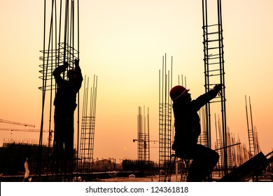 worker working with concrete iron near sunset
