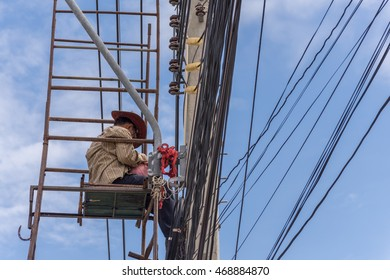 Worker working to install electric line by scaffolding on pickup truck