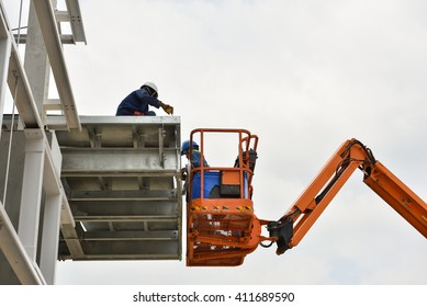 Worker working on Boom lift for Canopy roof frame on building
