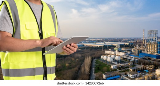 worker working on pad with oil and gas refinery background