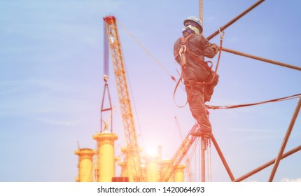 Worker working on scaffolding, worker on high in construction site wearing safety harness for safety concept.