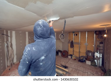 Worker is working with palette-knife for flattening the ceiling from wooden platform in room of apartment is inder construction, remodeling, renovation, overhaul, extension, restoration and