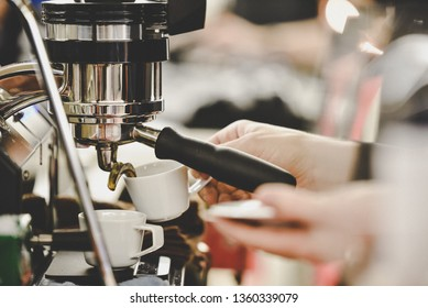 Worker works with a coffee machine