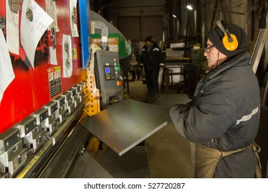 worker works for the machine CNC for bending metal
