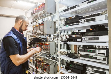 Worker works on the control panel in the data center. Specialist connects coaxial television wires in the rack of the TV station server room. Man switches  audio and video cable on the patch panel.