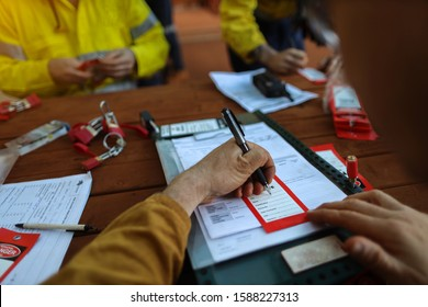 Worker writing they name on red danger tag and sign onto personnel red danger lock before placing locking into isolation permit safety control box prior start work each shift