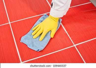 Worker with yellow gloves and blue towel clean red tiles grout from cement milk after grouting