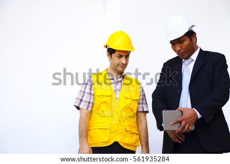 ddb5fa90e2d33 Worker in yellow hard hat is being briefed by Engineer in white hard hat.