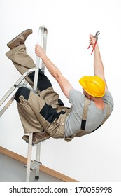 A worker with a yellow helmet falling from a metal ladder