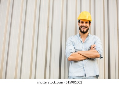 worker with yellow helmet and jeans shirt near a industrial wall, inspiring confidence