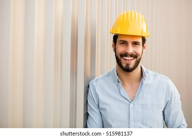 worker with yellow helmet and jeans shirt near a industrial wall