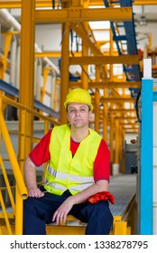 Worker in yellow reflective suit with yellow helmet sitting in a factory