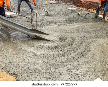 Workers adjust leveling of lean slab concrete with hoe.