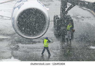 Workers of an airport in a snowstorm, with an aircraft in the background