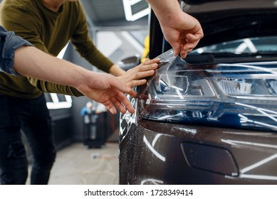 Workers applies car protection film on fender