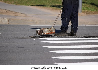 Workers apply a road marking to the pedestrian crossing zebra-stripe crosswalk with white paint and sprinkle the stripes with a reflective powder on the asphalt near the traffic light