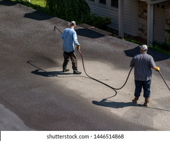 Workers applying blacktop sealer to asphalt street using a spray to provide a protective coat against the elements