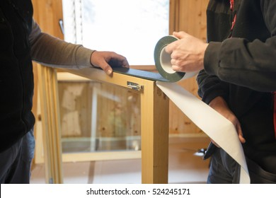 Workers applying a RAL self-adhesive insulating tape to install new, three pane wooden windows in a wooden house. Home renovation, sustainable living, energy efficiency concept.
