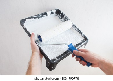 The worker's arm dips the roller into white paint to paint the wall