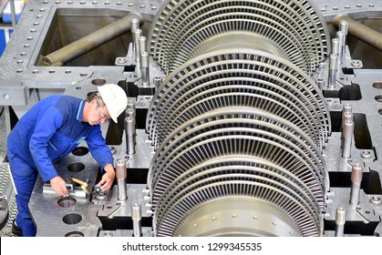 workers assembling and quality control of gas turbines in a modern industrial factory - checking dimensions with a measuring device