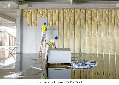 Workers are assembly gypsum wall. Plasterboard is under construction using wooden ladder.