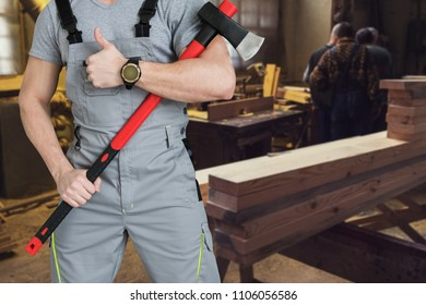 Workers with ax at the sawmill background.