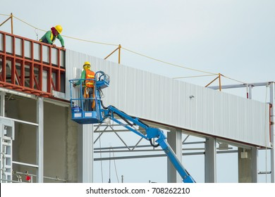 Workers in a baskets are installing sheet, building a factory.