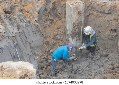 Workers are bending their heads using a concrete cutter to cut concrete piles and another person uses water to inject to reduce dust. On the muddy ground in the soil pit
