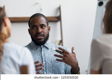Workers brainstorming at meeting, focus on black team leader telling ideas share information or business coach teach young company workers. Mixed race candidate during interview, hr and hiring concept