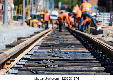 Workers in bright uniforms lay railway or tram tracks