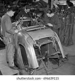 Workers building car in factory