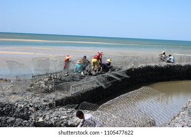 workers building sea breakwall. rock dam. Sea catastrophe. disaster prevention.