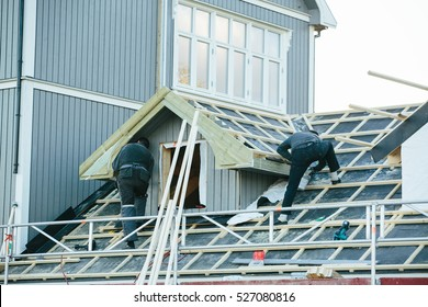Workers are building a wooden house. Roof repair.