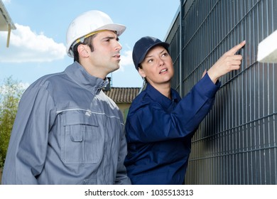 workers checking outdoors fence