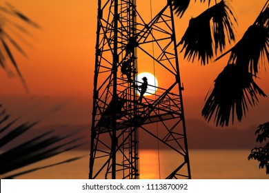 Workers are climbing to repair the telecommunication tower or poles, in the evening,Red sky sunset background.